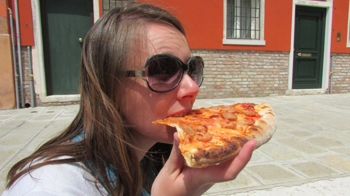 Munching on a big pizza slice. When in Italy, shove as much pizza in your face as you can!