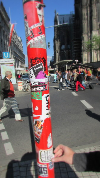 These are on a traffic light near the big Cathedral in Cologne. Quite a messy collection of stickers.