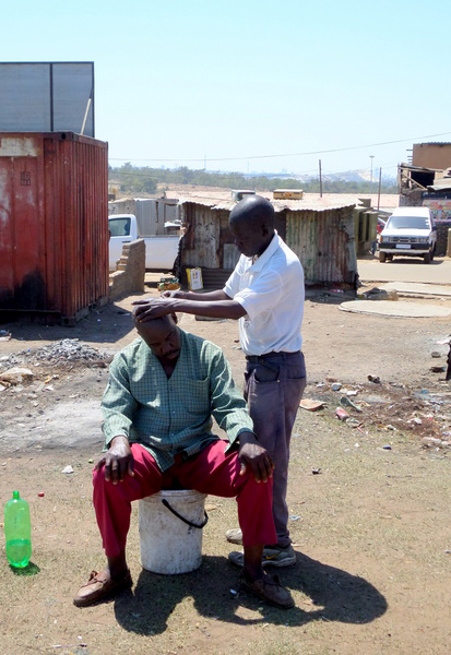 Just a normal day in Soweto, getting a Sunday haircut on the side of the road